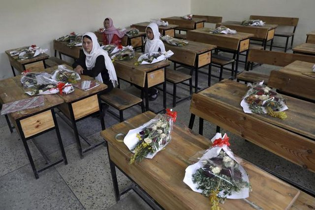 Деца стоят в класна стая заедно с букети на празни чинове, за да почетат убитите си съученици след атентата от 8 май. Снимка АП/БТА