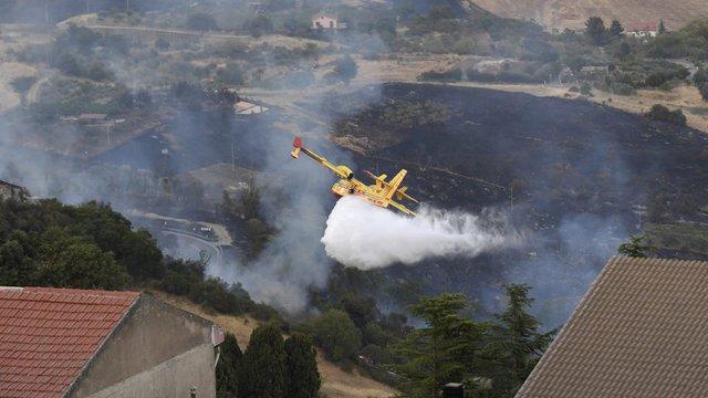 Канадски самолет изсипва вода над Петрала Сопрана, край Палермо, където множество пожари горят заради рекордно високите температури в Сицилия. Сн.AP