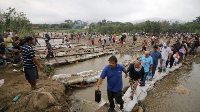 Венецуелци пресичат река, за да стигнат Колумбия. © Associated Press